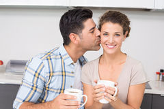 Cheerful woman drinking coffee getting a kiss from partner Royalty Free Stock Photos