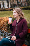 Cheerful woman drinking coffee and listening to music from tablet Royalty Free Stock Images
