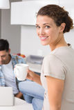 Cheerful woman drinking coffee while partners uses laptop Royalty Free Stock Photos