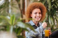 Cheerful woman drinking orange juice in cafe with green plants Stock Photo