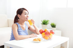 Cheerful woman drinking an orange juice Stock Image