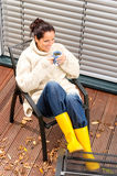 Cheerful woman drinking tea autumn rubber boots Stock Photography
