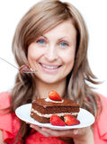 Cheerful woman eating a cake Stock Photography