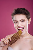 Cheerful woman eating chocolate bar. Nice beautiufl woman smiling and eating chocolate bar while standing  on pink background Royalty Free Stock Image