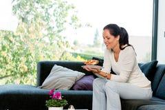 Cheerful woman eating homemade sandwich living room Stock Image