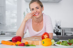 Cheerful woman eating vegetables Stock Images