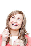 Cheerful woman eating a yogurt. Against a white background Royalty Free Stock Photos