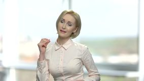 Cheerful woman in elegant blouse is dancing. Attractive middle-aged blonde woman is dancing and snapping fingers on blurred background stock footage
