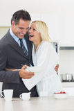 Cheerful woman embracing well dressed man in kitchen Stock Photography