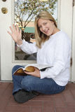 Cheerful woman employee waiting outdoors & waving Stock Photo