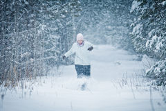 Cheerful Woman Enjoying the joys of Winter. Cheerful Woman Running in Forest and Enjoying the joys of Winter Royalty Free Stock Photography