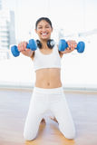 Cheerful woman exercising with dumbbells in fitness studio Stock Photo