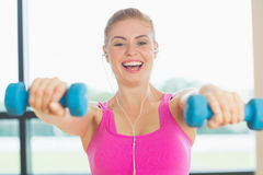 Cheerful woman exercising with dumbbells in fitness studio Stock Photos