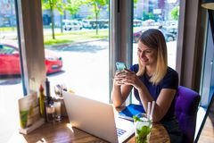 Cheerful woman experienced business writer for executive summary reading e-mail on mobile phone after work on laptop computer. Sitting in coffee shop near stock photo