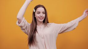 Cheerful woman in fashion pastel shirt stretched, keeping hand above head