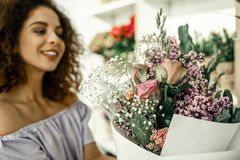 Cheerful woman feeling amazing after making beautiful bouquet for client royalty free stock images