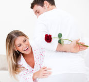 Cheerful woman finding a rose bahind her husband Stock Photo