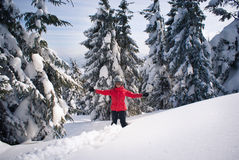 Cheerful woman among fir trees in the snow Stock Photo