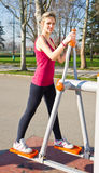 Cheerful woman in fitness wear exercising with equip Stock Image