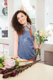 Cheerful woman florist choosing flowers and making bouquet in shop Royalty Free Stock Images