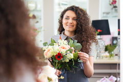 Cheerful woman florist holding flower bouquet and looking at mirror Stock Photo