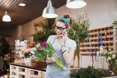 Cheerful woman florist holding tulips and talking on mobile phone Royalty Free Stock Image