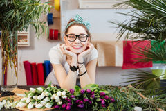 Cheerful woman florist selling tulips in flower shop Stock Photos