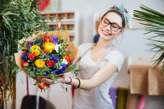 Cheerful woman florist showing bouquet of colorful flowers Royalty Free Stock Photos