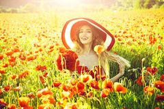 Cheerful woman on a flower field. girl in field of poppy seed in retro hat. Cheerful woman on a flower field. girl with long curly hair in red dress and retro stock photo