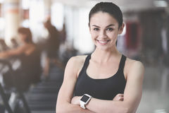 Cheerful woman folding arms in gym. royalty free stock photos