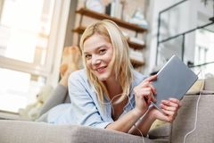 Cheerful woman with gadget resting at home Royalty Free Stock Photo