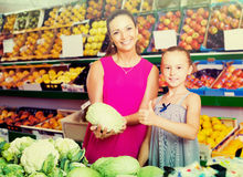 Cheerful woman with girl buying cabbage in grocery shop Stock Image
