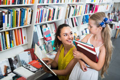 Cheerful woman with girl looking in open book Stock Image