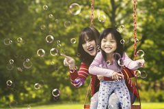 Cheerful woman and girl playing bubbles Stock Photo