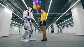 Cheerful woman giving balloons to automated droid. stock footage