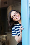 Cheerful woman in glasses looking out of cafe and smiling Stock Photos
