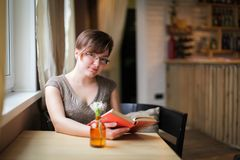 Cheerful woman in glasses sitting near window reading book Royalty Free Stock Image