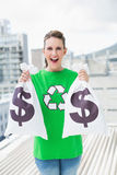 Cheerful woman in green recyling tshirt showing money bags Royalty Free Stock Photos