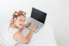 Cheerful woman in hair curlers using laptop in bed Stock Photos