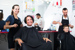 Cheerful woman hairdresser cutting female client Stock Photos