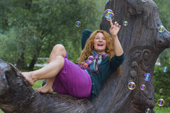 Cheerful woman having fun with soap bubbles in park Royalty Free Stock Photos