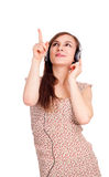 Cheerful woman with headphones ponting up Stock Photo