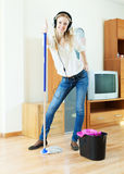 Cheerful woman in headphones washing floor with mop Royalty Free Stock Photo