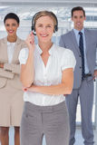 Cheerful woman with headset standing in front of business people Royalty Free Stock Photos