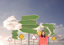 Cheerful woman with her arms raised up. Composite image of cheerful woman with her arms raised up in front of road signs in sky Royalty Free Stock Photography