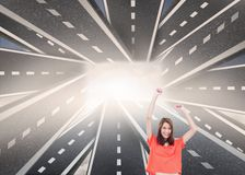Cheerful woman with her arms raised up. Composite image of cheerful woman with her arms raised up in front of streets running together in the middle Royalty Free Stock Images