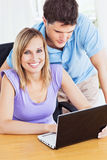 Cheerful woman and her boyfriend using a laptop. Portrait of a cheerful women and her attentive boyfriend using a laptop in the living-room Stock Photography