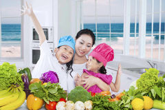 Cheerful woman and her kids cook vegetables Stock Images