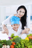 Cheerful woman and her son making salad. Portrait of beautiful women and her son cooking vegetables salad in the kitchen while smiling at the camera Stock Photos