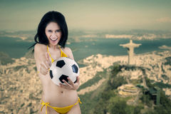 Cheerful woman holding ball in Brazil. Portrait of sexy woman wearing bikini holding a soccer ball Stock Photos